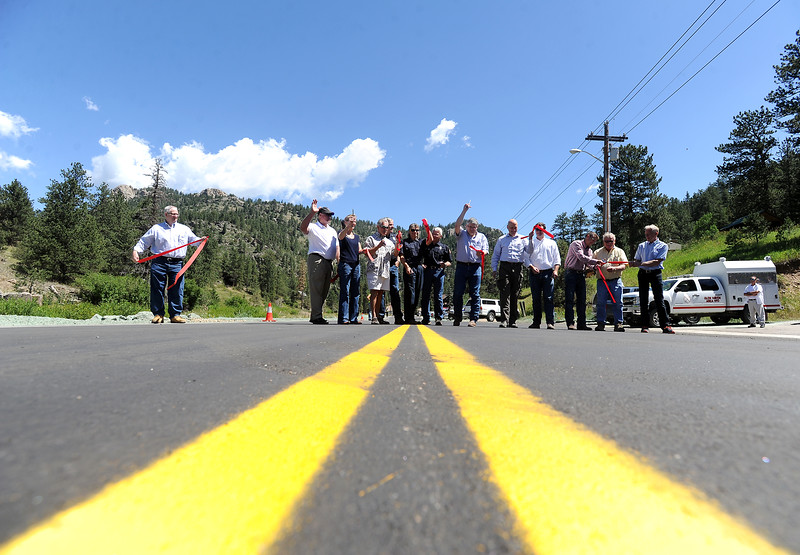 Larimer county Commissioners Tom Donnelly and Steve Johnson, Federal Highway Administration officials, Glen Haven Residents and more cut the ribbon to open County Road 43 in Glen Haven Thursday, July 14, 2016. The road, which was damaged during the flood in 2013, reopened after it was reconstructed. (Photo by Jenny Sparks/Loveland Reporter-Herald)