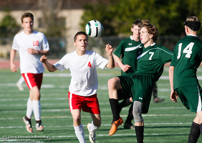 Las Plumas's Esteban Farias (left) looks to the ball as Paradise's Gabe Price reaches up for the kick during a boys soccer game January 30, 2017 in Oroville, California. (Emily Bertolino -- Enterprise-Record)