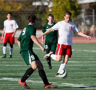 Las Plumas's Parker Paul (12) kicks the ball past Paradise's defense Nick Gomez (9) during a soccer game January 30, 2017 in Oroville, California. (Emily Bertolino -- Enterprise-Record)