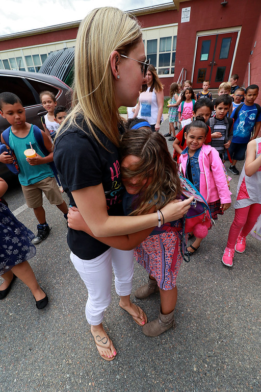 . Fitchburg Crocker Elementary School first grade teacher Lea LaFond gets hug from one of her students  as they make their way to the buses on the last day of school at T.C. Passios Elementary School in Lunenburg where they spend much of the school year after Crocker was closed. SENTINEL & ENTERPRISE/JOHN LOVE