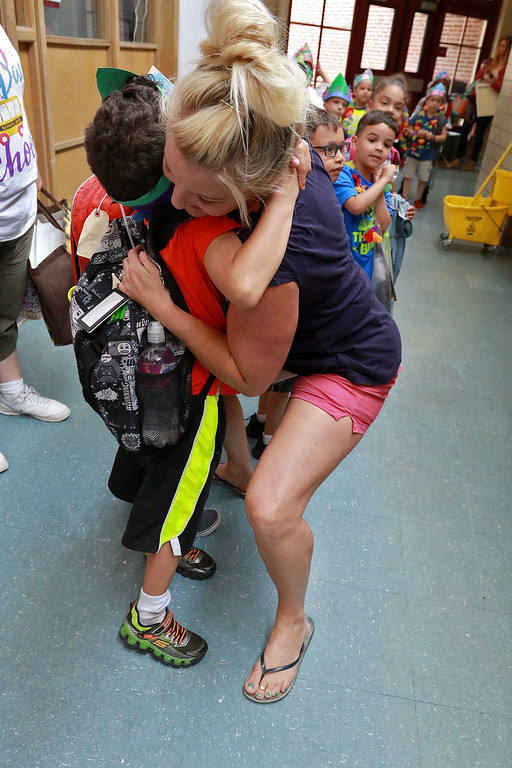 . Fitchburg Crocker Elementary School Kindergarten teacher Jennifer Aronow got hugs from her students as they make their way to the buses on the last day of school at T.C. Passios Elementary School in Lunenburg where they spend much of the school year after Crocker was closed. SENTINEL & ENTERPRISE/JOHN LOVE