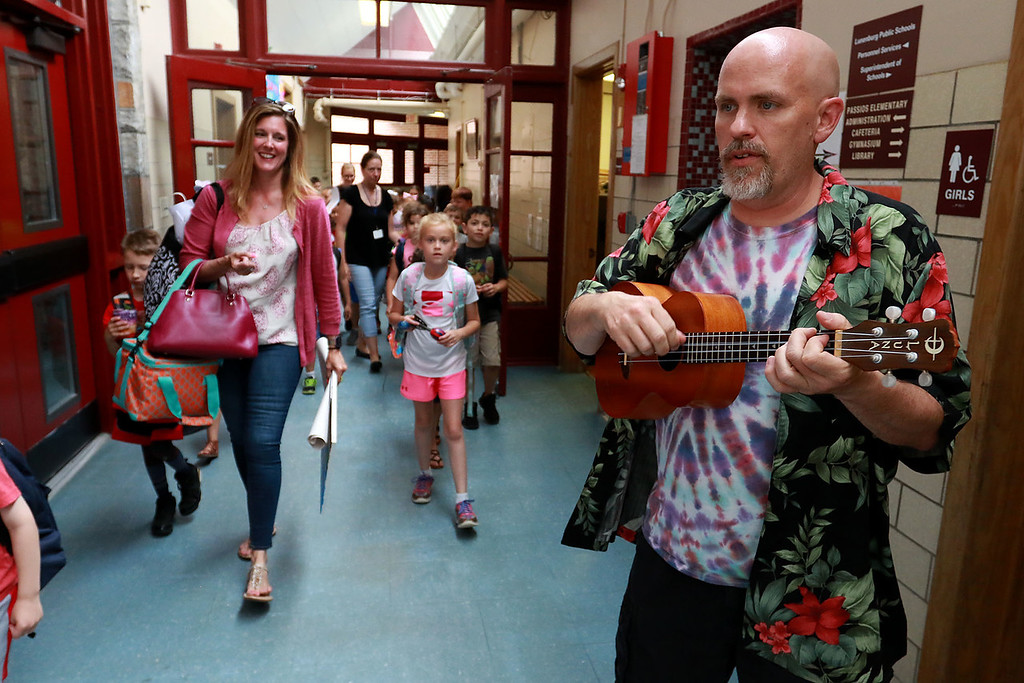 . Fitchburg Crocker Elementary School music teacher Aaron Clark plays the ukulele for the students as they make their way to the buses on the last day of school at T.C. Passios Elementary School where they spend much of the school year after Crocker was closed. SENTINEL & ENTERPRISE/JOHN LOVE