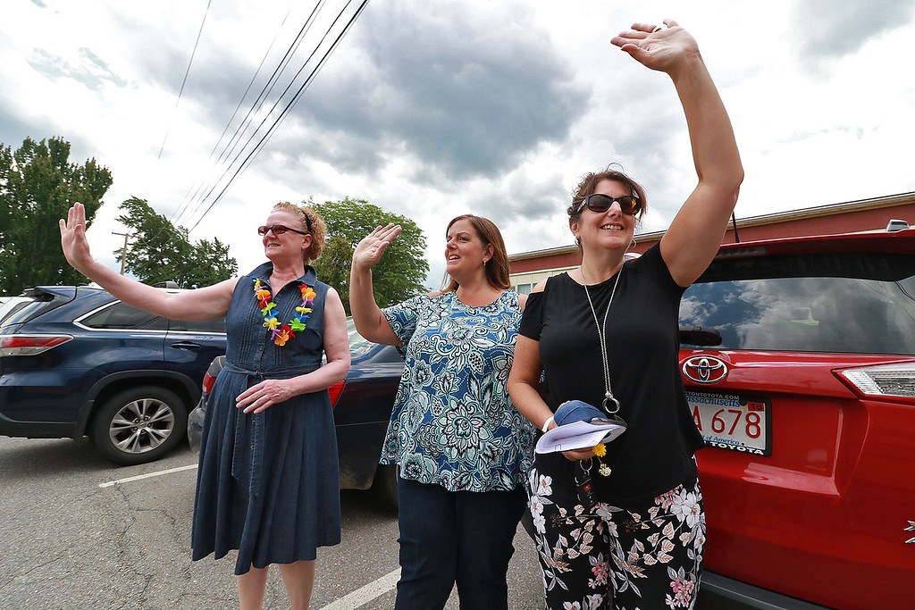 """. Fitchburg Crocker Elementary School second grade teachers Patty Marsh, Robin Bachant and Sherry Carlson wave to the kids as the buses pull away on the last day of school at T.C. Passios Elementary School in Lunenburg where they spend much of the school year after Crocker was closed. Her shirt read \""""Happy last day of school.\"""" SENTINEL & ENTERPRISE/JOHN LOVE"""