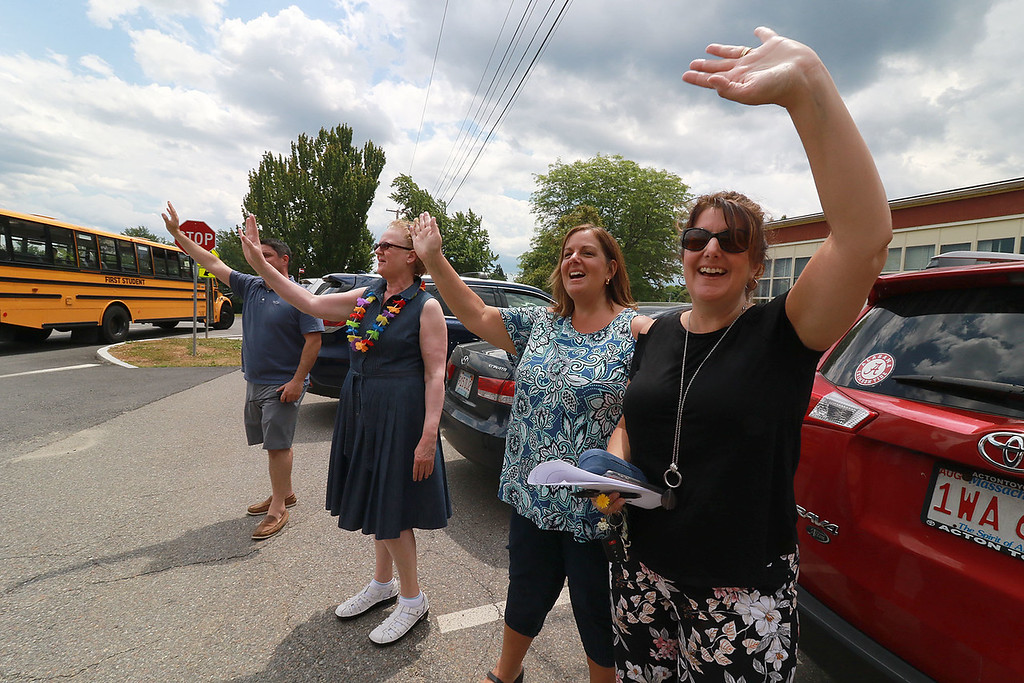 """. Fitchburg Crocker Elementary School Principal Adam Renda along with second grade teachers Patty Marsh, Robin Bachant and Sherry Carlson wave to the kids as the buses pull away on the last day of school at T.C. Passios Elementary School in Lunenburg where they spend much of the school year after Crocker was closed. Her shirt read \""""Happy last day of school.\"""" SENTINEL & ENTERPRISE/JOHN LOVE"""