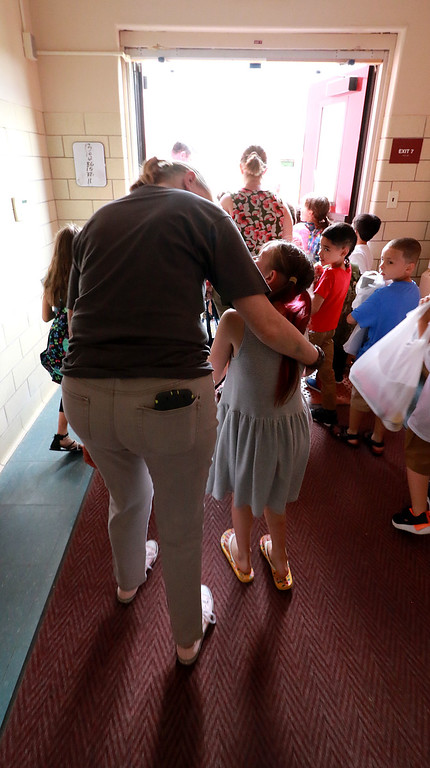 . Fitchburg Crocker Elementary School special education teacher Bridget Szlachtowski chats with a student as she walks her out to the buses on the last day of school at T.C. Passios Elementary School in Lunenburg where they spend much of the school year after Crocker was closed. SENTINEL & ENTERPRISE/JOHN LOVE