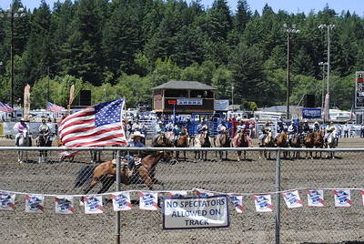 Rodeo contestants line up for the National Anthem as a woman and her horse sprint around the group with an American flag at the beginning of the Sunday Fortuna Rodeo field events. (Hunter Cresswell -- The Times-Standard)