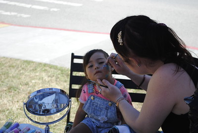 Callie Perrott paints a glittery dolphin on Arianah's face on Sunday during the 96th Fortuna Rodeo. (Hunter Cresswell -- The Times-Standard)