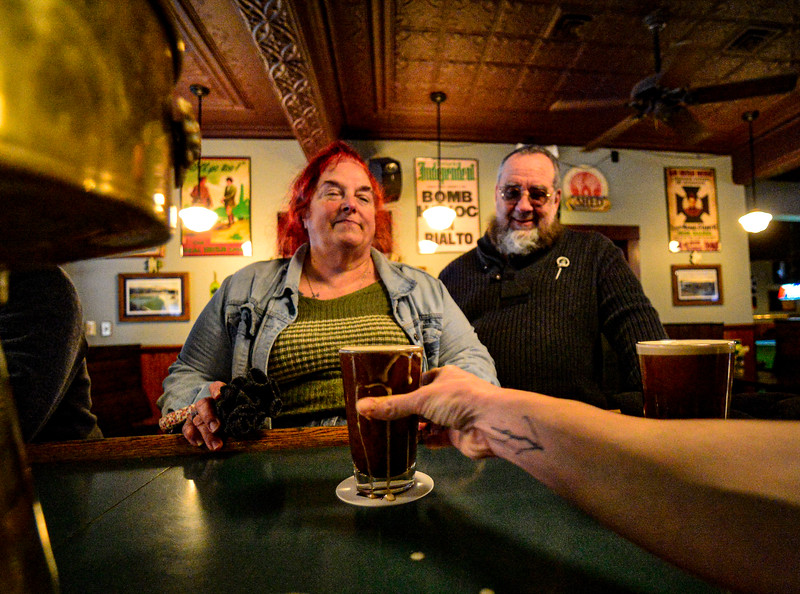 KRISTOPHER RADDER — BRATTLEBORO REFORMER<br /> Cameron O'Brien, a bartender at Donovan's, in Bellows Falls, Vt., pours a pint of Guinness for Deb and Case Wright, of Bellows Falls, before the state-ordered closure of all bars and restaurants for dine-in experience at 2 p.m. Tuesday, March 17, 2020, because of the COVID-19 outbreak.