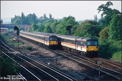 73209 approaches Gatwick Airport whilst working the 1815 London Victoria-Gatwick airport service and passes 73212 'Airtour Suisse' working the 1835 Gatwick Airport-London Victoria service on 26/05/1992. Horley station can be seen in the background.