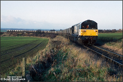 Having left the ex Midland Railway Clowne Branch at Oxcroft Colliery Branch Jnct (behind the rear wagon), 58024 begins its short journey down to Oxcroft Opencast Disposal Point with a rake of empty HAA 'merry go round' coal hoppers for loading on 19/11/1992. Oxcroft closed in 2006, along with the disappearance of mines in Derbyshire. It was briefly reopened by UK Coal when they started a coal recovery operation in 2007 to sift through nearby pit tips and recover around 14000 tonnes of coal. It closed again shortly after and is now flattened and all track lifted.