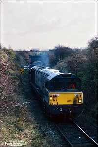 58018 'High Marnham Power Station' heads up the branch from Oxcroft Opencast Disposal Point towards Oxcroft Colliery Branch Jnct on 19/11/1992 with a train of HAA 'merry go round' coal hoppers for Cottam Power Station. Oxcroft closed in 2006, along with the disappearance of mines in Derbyshire. It was briefly reopened by UK Coal when they started a coal recovery operation in 2007 to sift through nearby pit tips and recover around 14000 tonnes of coal. It closed again shortly after and is now flattened and all track lifted.