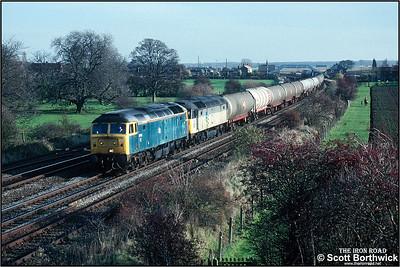 47115+47221 pass Knabbs Bridge, Melton Ross whilst working 6L33 1238 Lindsey Oil Refinery-Leeds ORT on 19/11/1990.