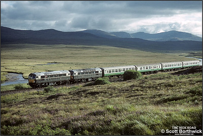 Running through the somewhat barren landscape near Achanalt, 26001+26007 glint in the evening sunshine as they head back to Inverness with 2H86 1705 Kyle of Lochalsh-Inverness on 25/08/1993.