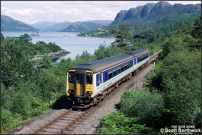 Due to the failure of one of the two sprinters on the morning Wick/Thurso-Inverness service resulting in too few seats being available for the return service, the diagramed  loco and stock for this Kyle Line working were instead sent to Wick with the remaining servicable Sprinter 156477, being sent to Kyle, seen here passing Plockton whilst forming 2H85 1235 Inverness-Kyle of Lochalsh on 13/07/1993.