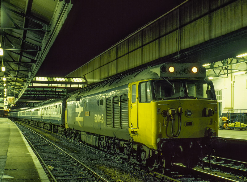 """50048 """"Dauntless"""" at Exeter St Davids with the ECS for 2O96, <br /> the 20:24 service to Basingstoke, on 24th November 1984. Scanned Transparency."""