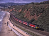 """47747 """"Graham Farish"""" passing Langstone Rock, at Dawlish Warren, with 1M56, <br /> the 08:46 Penzance - Manchester, on 20th September 2001. Scanned Transparency."""