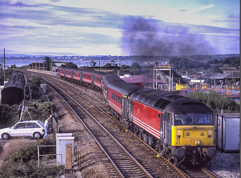 """47814 """"Totnes Castle"""" gets away from station stop at Dawlish Warren, with 1V50, the 08:40 Glasgow - Paignton, on 1st September 2001. Note the fellow enthusiast on the car roof. Scanned Transparency."""
