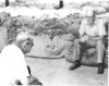 men sitting on tobacco bundles  - JC