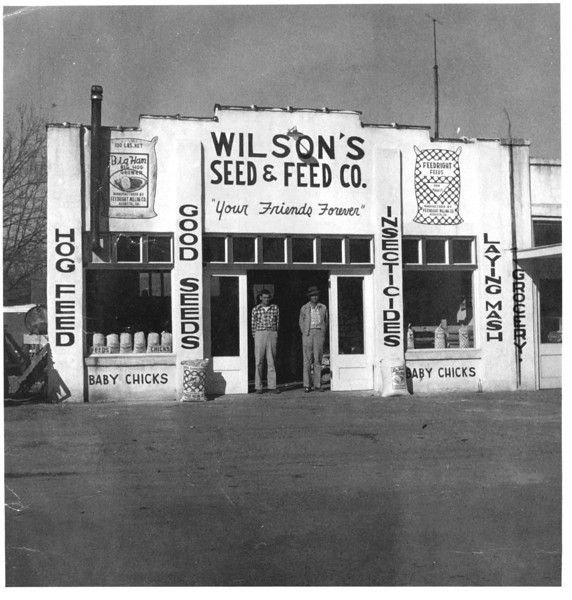 Wilson's Seed and Feed Store on East Marion. Photo most likely taken by Jamie Connell.<br /> Identificaction of men in doorway is needed.