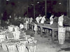 LIBERTY WHSE. 1950 L.R. STALLINGS (WITH WHITE HAT & CIGAR), PREACHER SHAW AT END OF TABLE. WOMEN WERE WRAPPING TOMATO & PEPPER PLANTS FOR STALLINGS PLANT FARM.