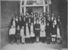 Jennie Mae Scruggs' Music Class at Nashville Public School <br /> <br /> Mrs. Scruggs' music class, posed at east side entrance to old Nashville School.  I'm thinking it was during one of the recessions -- note the 2 little waifs on front row with sweaters on, but no shoes.<br /> Mrs. Scruggs is in back row, 3rd from right.<br /> Is that Mary Ernest Perry in back row, head against door?<br /> Possibly Ruby Gaskins Turner, 2nd row, 3rd from right?<br /> <br /> (photo and information courtesy of Jan Scruggs Rowe)