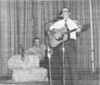Roberson Gaskins with guitar and his brother, Walter Gaskins seated. From a newspaper clipping. Original photo needed.