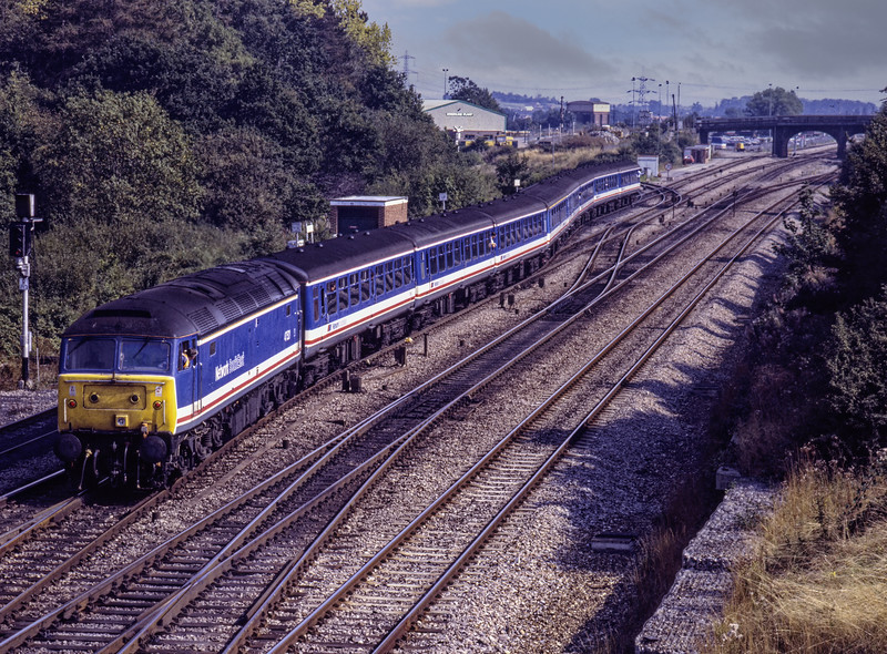 On 9th September 1991, due to a points failure at Didcot East Junction, 47521 with 1F24, <br /> the 13:20 Paddington - Oxford, was diverted via Foxhall Junction. It is shown here setting back to Parkway Station, to gain access to the Oxford line. Scanned Transparency.