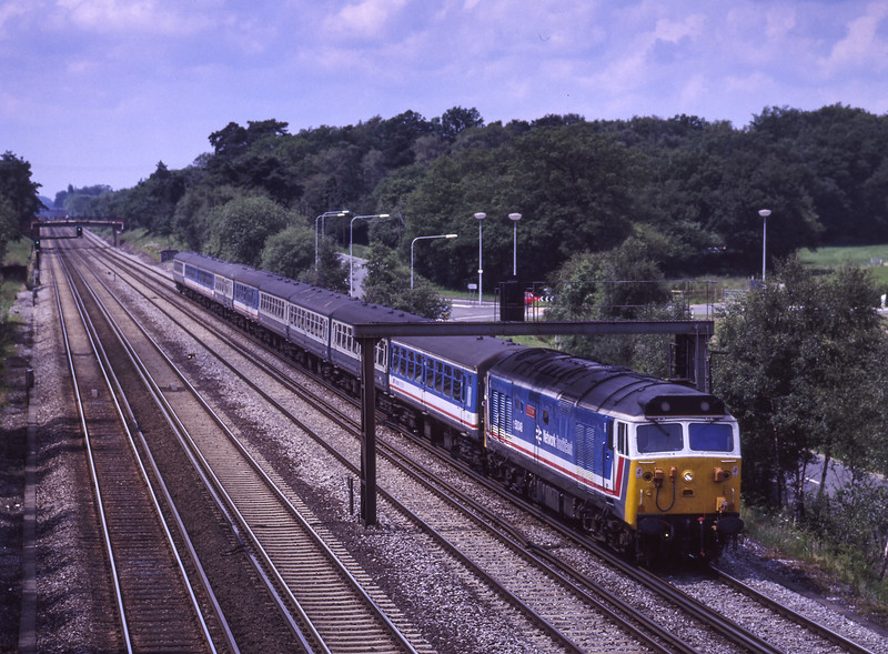 """50048 """"Dauntless"""" at Summit Avenue, Fleet, with 1O15, the 09:35 Exeter St Davids - Waterloo, on 14th June 1987. Scanned Transparency."""