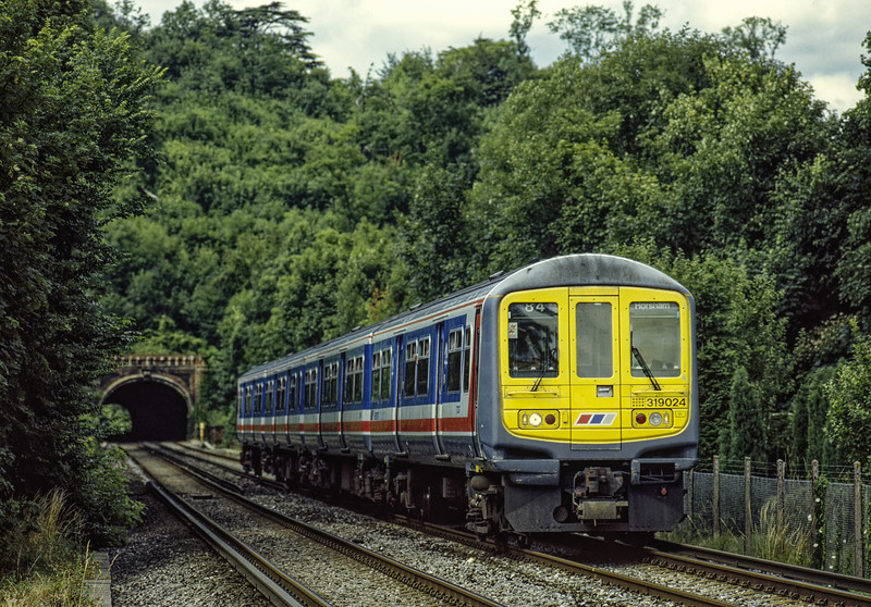 319024 exits Mickleham Tunnel with a Thameslink service to Horsham, on 17th July 1993. Scanned Transparency.