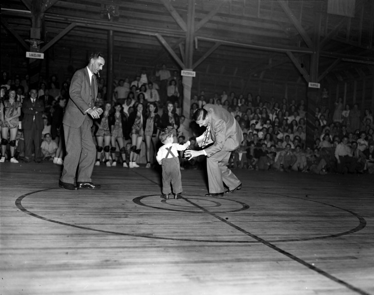 Nashville High School, old gymnasium, February 1948<br /> <br /> The Nashville Herald, front page, March 4, 1948<br /> Photo caption:<br /> HELPING OUT – Young Sam Mashburn, son of the superintendent of Ray City school, is starting out early in learning the phases of the profession.  After the tournament finals here last week, he made careful examination of each of the trophies and then got a little practice in presentation.  Here he's giving one to Supt. O.E. Hendley, Nashville, who in turn awarded them to teams in the finals. – Photo by Jamie Connell.<br /> <br /> (A tightly cropped version of this photo showing only young Mashburn and Mr. Hendley was used for publication.)