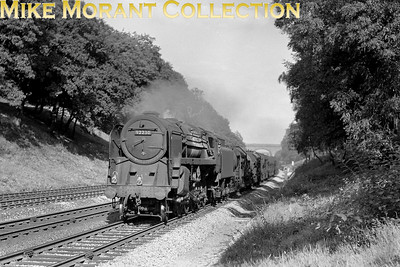 BR Standard 9F 2-10-0 no. 92230is in charge of a rake of m,ilk tank wagons on the down main line as it passes through Sonning Cutting near Woodley. 92230 has an 81A Old Oak Common shed plate which narrows the date to between 11/58 and 1/60. [Mike Morant collection]