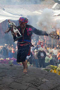 Man holding the patron saint of his cofridia, dancing and setting off fireworks before going into the church in Chichicastenango.