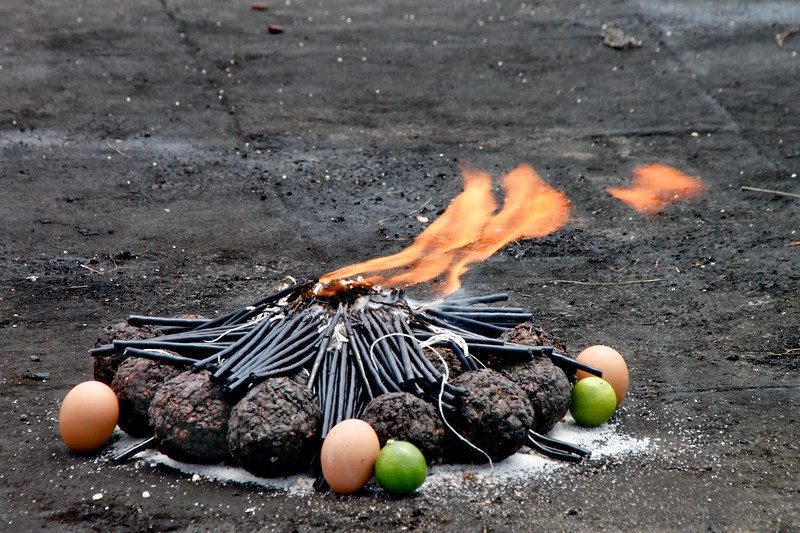 So what do you do if people are talking about you at work, spreading rumors and gossip, none of it is true but yet you're worried about losing your job. If you are a Mayan living in Guatemala, you head to the nearest altar dedicated to San Simon, and fire up an offering like this...black candles cast out rumor and gossip, the limes help cut the power of the gossip, the eggs remove evil spirit, and then light on fire with a whole bunch of black incense balls.