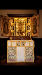 Altar with white damask and Portuguese tapestry frontal