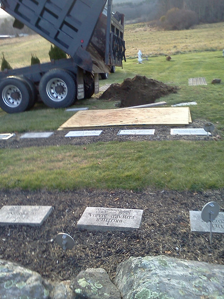 A truck dumps dirt to fill in Brother Ambrose's grave. <br /> Credit: Roseanne T. Sullivan