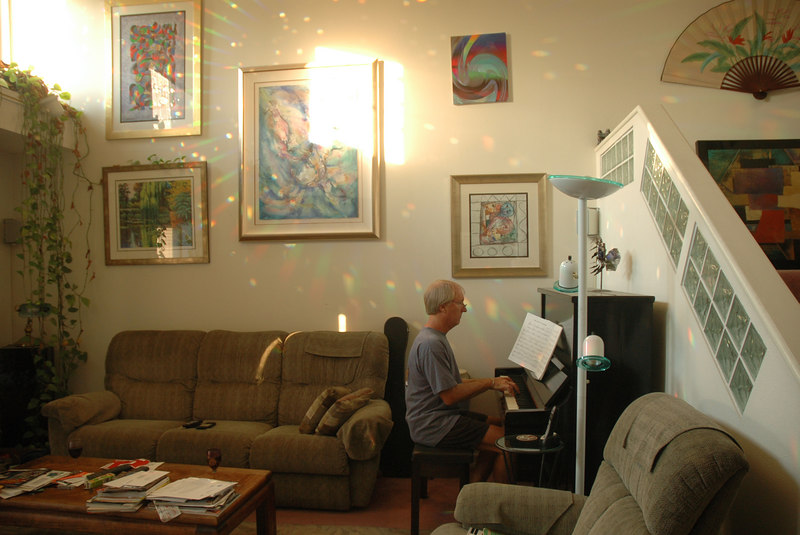 Ted playing piano in his livingroom, above him is a painting by Fred.  The spray of rainbows and light in the wall seem to be the notes he plays. Taken today, 9-12-06.