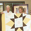 From left, Rob Greuel, Leonard Greuel, Lisa Lustig, Lauren Greuel and LeeAnn Greuel hold up a quilt raffled off 20 years ago to help raise funds for Lauren's treatment during  a celebration of her 21st birthday of Lauren Greuel at the First Mid-America Bank and Trust in Neoga on Friday, June 8, 2018. Lauren was born with multiple life-threatening disorders and was not expected to live past age seven. Graham Milldrum photo