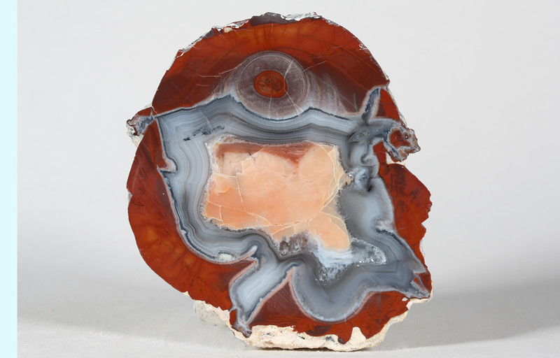 "#A048 Thunder Egg, Lava Cap Claim, Little Florida Mtns., Deming, New Mexico USA<br /> Is this a chubby lady dancing in a pink chamise or am I a bit over the top? For sure it is a fine fortification agate with an opal center.<br /> 3 x 2 1/4 x 1 1/4"" 0.31 lb<br /> All agates in the Sample Gallery have been sold."