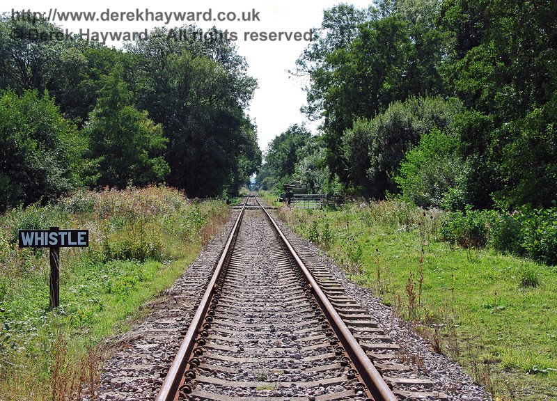 This view looks back south along the line towards the crossing.  Trains give a good loud blast on the horn or whistle, but the cattle in the adjacent field were very unimpressed.  They are obviously used to engines and loud noises. 02.09.2007