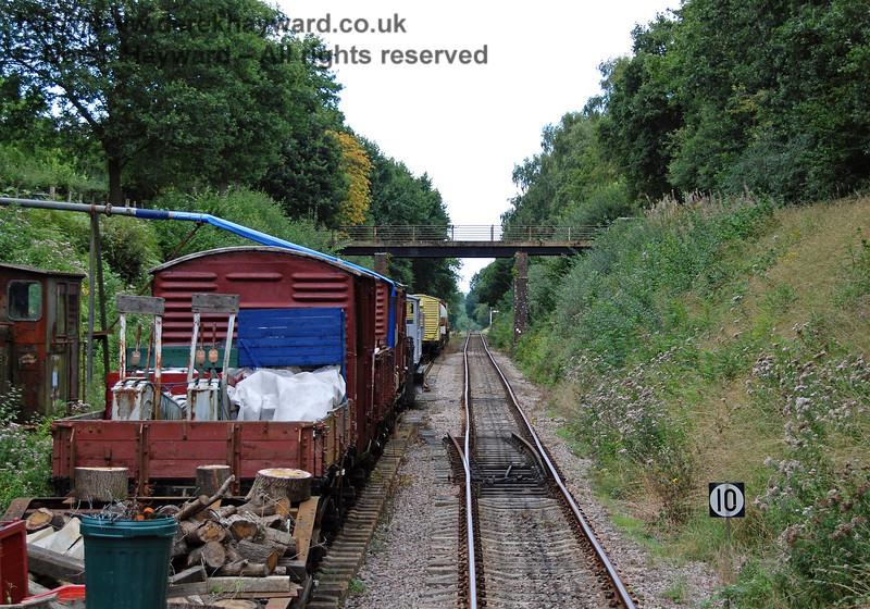Passing the siding, this view from the front of a train shows the line entering a cutting.  Disused points are ahead, and on the extreme left a rusting diesel shunter in exceptionally poor condition can just be seen behind the shed in a second siding. 02.09.2007
