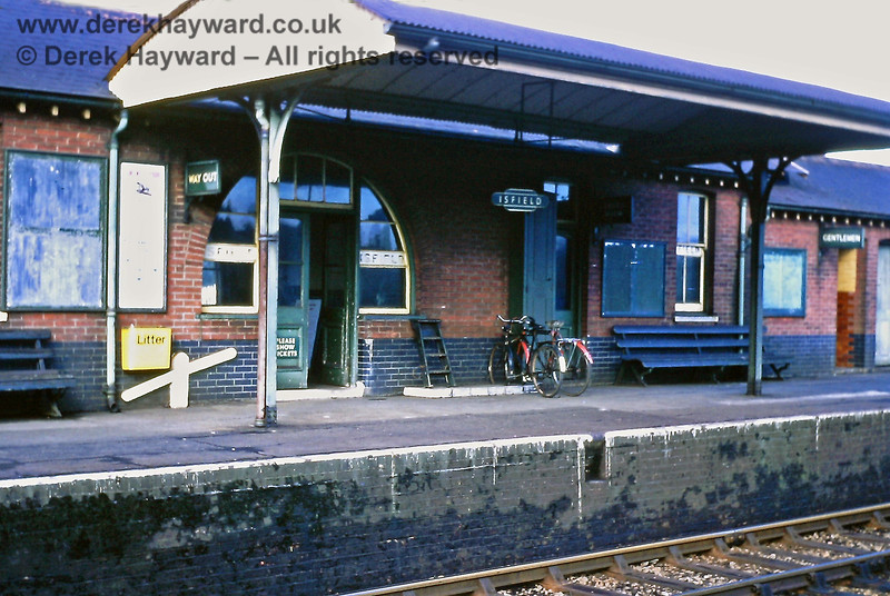 Part of the Up side Isfield station building, including the booking office.  A few bicycles are in the racks, but the bright yellow litter bin may not enhance the period atmosphere. 23.02.1969.  Eric Kemp retains all rights to this image.