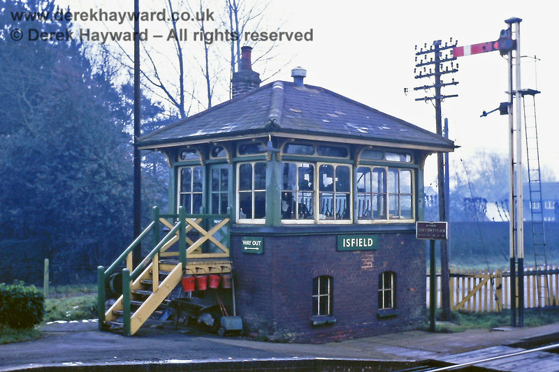 Isfield signal box and Down starting signal, pictured on 01.01.1969. The station had no footbridge and the way out was across the board crossing.   Eric Kemp retains all rights to this image.