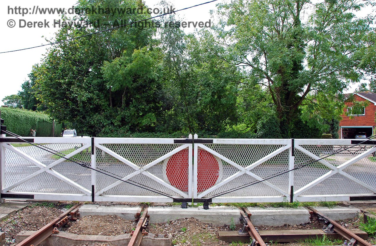 A view south across the disused crossing.  The trees denote the boundary of a private garden across the road.  The second level crossing gate is still in situ on the other side of the road, but unfortunately in poor condition. 02.09.2007