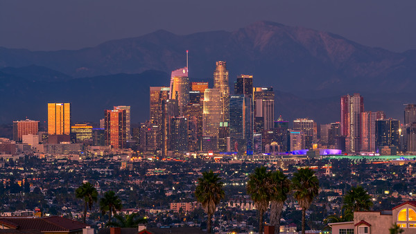 Los Angeles skyline at sunset with snow capped mountains in the background