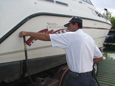 After cleaning the exterior of this boat, Wahweap Marina employee Kemp Wilson sends scalding hot water into a port that leads to the boatÕs engine and bilge. Before coming to Lake Powell, this boat had been on Lake Pleasant, a mussel-infested water in Arizona.  Photo by Wayne Gustaveson, Utah Division of Wildlife Resources on 8-12-08.