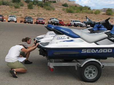 Utah Division of Wildlife Resources Technician Roas Hoban (closest to the camera) and Starla Burton with the National Park Service examine a personal watercraft for mussels. This photo was taken at the Wahweap Marina at Lake Powell.  Photo by Wayne Gustaveson, Utah Division of Wildlife Resources.