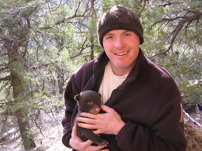 Officer Justin Shirley with a black bear cub