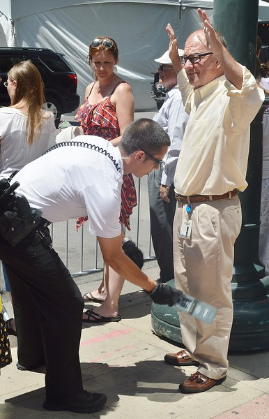 "Secret Service agent using ""wand' to screen man outside event featuring President Obama."