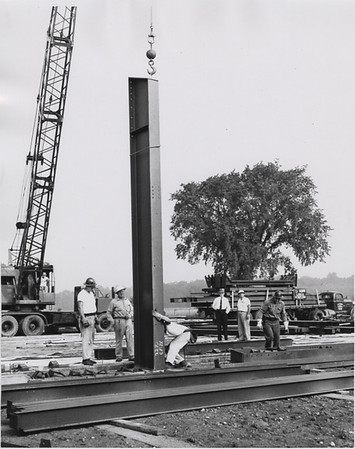 Construction workers put up the steel beam for Alumni Gym project.