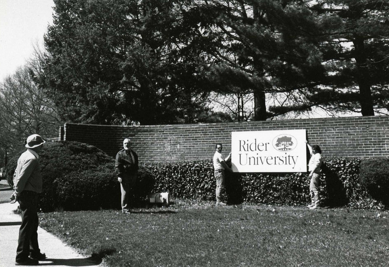 New signage for the front gate is positioned on the brick entrance. The signage is reflective of the fact that Rider has university status, effective April 14, 1994.